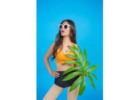 一位身穿泳衣手持绿叶的美女在蓝色上摆姿_5219566
