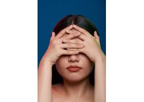 一名亚裔女子在摄影棚摆姿势用交叉的手指_5576503