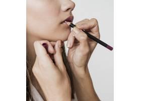一名女子在模特身上涂唇线_5823390