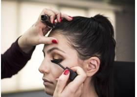 一名女子在模特身上涂睫毛膏_5823360
