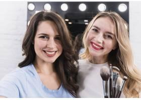 两个微笑的女人拿着刷子在化妆镜前自拍_4360970