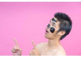在脸上涂上黑色化妆品的帅哥用粉色摆出各_5598355
