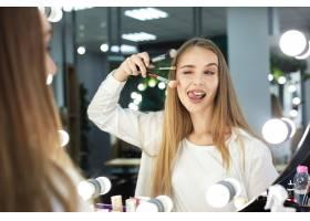 一名女子拿着化妆刷做鬼脸_5863617