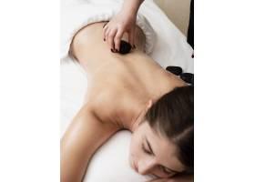 一名女子在水疗中心接受加热岩石疗法_6053280