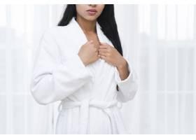 一名女子在水疗中心穿着浴袍摆姿势_4837780