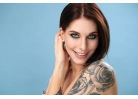 蓝眼睛和玫瑰色纹身的女人微笑着_8909315