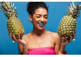 蓝色墙壁上方双手分开拿着两个多汁的菠萝_6729911