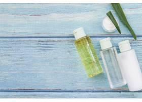 蓝色纹理木质背景上的芦荟喷雾瓶和保湿霜_3706412
