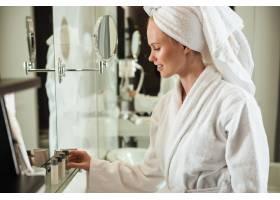 身着浴袍的女子在镜子旁看化妆品_7704257