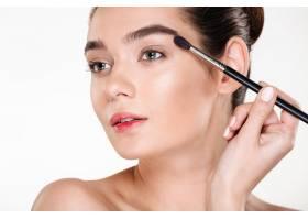 魅力时尚女性黑发发髻用刷子涂眼影的健康与_6514488