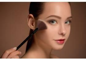 拿着化妆刷的美女完美的皮肤化妆_9368070