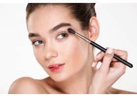 用刷子涂抹眼影的性感女人的特写照片皮肤_6514487