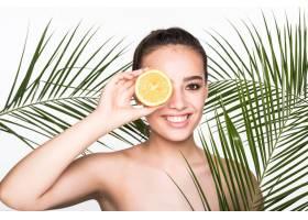 皮肤完美的年轻女子手持柑橘类水果周围环_8990742