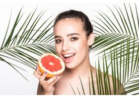 皮肤完美的年轻女子手持柑橘类水果周围环_8990759