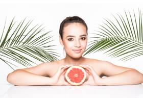 皮肤完美的年轻女子手持柑橘类水果周围环_8990768