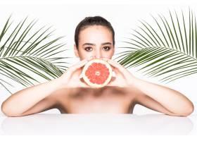 皮肤完美的年轻女子手持柑橘类水果周围环_8990771