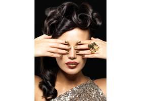 美丽的女人涂着金色的指甲和富有创意的口_11994030