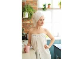 洗澡后厨房里的女人用毛巾盖着身体_8424431