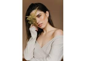穿着舒适衣服的快乐的高加索女子拿着植物_12608179
