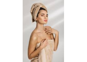 洗澡后用毛巾盖着站着的美丽时髦的年轻女子_8358085