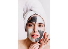 绿眼女孩正在白墙上做水疗美容戴着泥土面_12607835