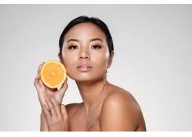 美丽沉着的女人拿着橘子片和看起来像是相机_6604886