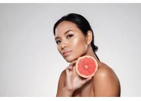 美丽沉稳的女人展示葡萄柚片_6604887