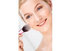 女人用刷子在脸上化妆_9228595