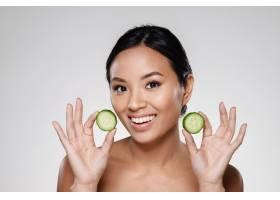 年轻漂亮的女士拿着黄瓜片_6604875