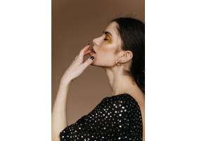 性感的欧洲模特戴着金色的饰品站在棕色的墙_12608126