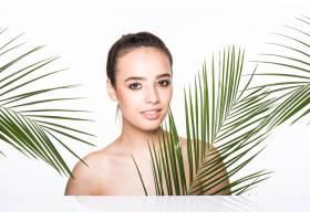 年轻的美女拿着绿色的棕榈叶摆姿势_8990712