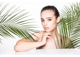 年轻的美女拿着绿色的棕榈叶摆姿势_8990728