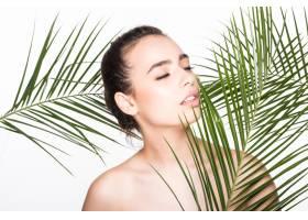 年轻的美女拿着绿色的棕榈叶摆姿势_8990732