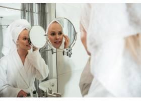年轻的金发女子照镜子涂抹化妆品_7704258