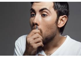 年轻英俊的男子在灰色的墙壁上用镊子夹着鼻_8083932