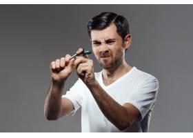 年轻英俊的男子试图打破灰墙上的剃须刀_8083956