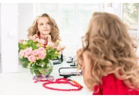 一个带着化妆品的小女孩坐在镜子旁边_7020829