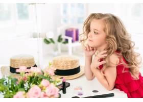 一个带着化妆品的小女孩坐在镜子旁边_7020830