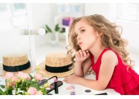 一个带着化妆品的小女孩坐在镜子旁边_7020831