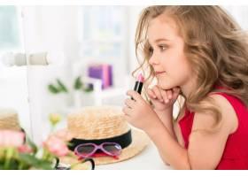 一个带着化妆品的小女孩坐在镜子旁边_7027928