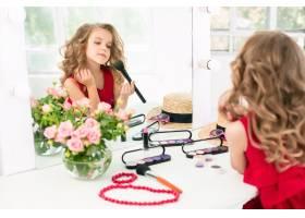 一个带着化妆品的小女孩坐在镜子旁边_7027929