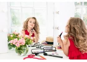 一个带着化妆品的小女孩她在妈妈的卧室里_8923796