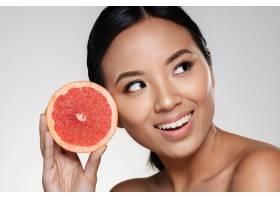 一位美丽的亚洲女士在一旁看着拿着柚子片_6604888
