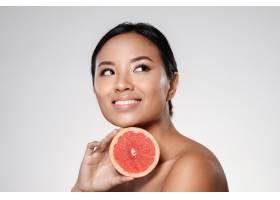 一位美丽的亚洲女士在一旁看着拿着柚子片_6604889