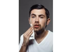 一名不高兴的年轻人在翻墙刮胡子后摸了摸脸_8083993