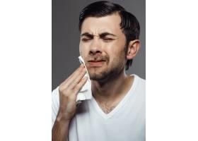 一名不高兴的年轻人在翻墙刮胡子后摸了摸脸_8083996