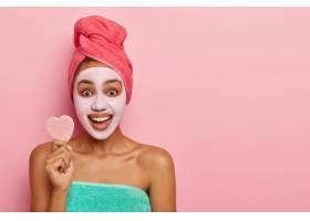 乐观的女人拿着柔软的小海绵进行面部护理_12495684