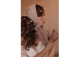 卷发女子侧面肖像深色头发的鲜花摆在米色_12677793