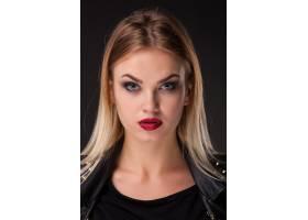黑色墙上留着长长金发的漂亮模特的肖像_6755916