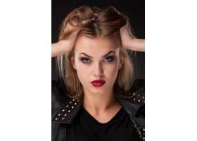 黑色墙上留着长长金发的漂亮模特的肖像_6755917